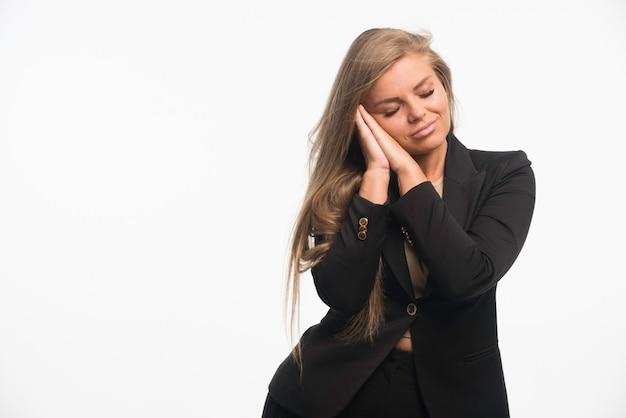 Jonge zakenvrouw in zwart pak ziet er dromerig uit Gratis Foto