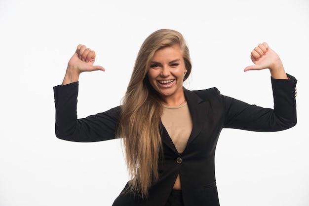 Jonge zakenvrouw in zwart pak ziet er zelfverzekerd uit en wijst zichzelf terwijl ze glimlacht Gratis Foto