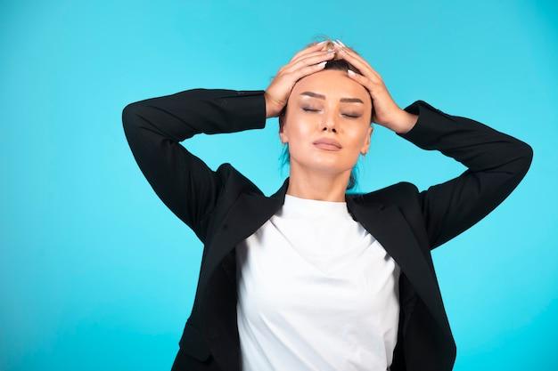 Jonge zakenvrouw in zwarte blazer met hoofdpijn. Gratis Foto