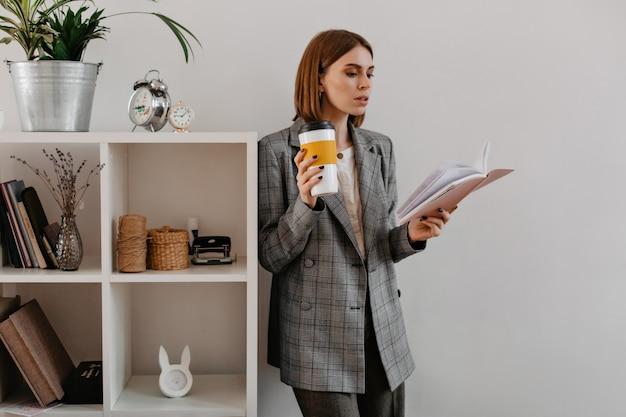 Jonge zakenvrouw met glas koffie in haar handen, gefascineerd door lezen, staat leunend op de plank met werkaccessoires. Gratis Foto