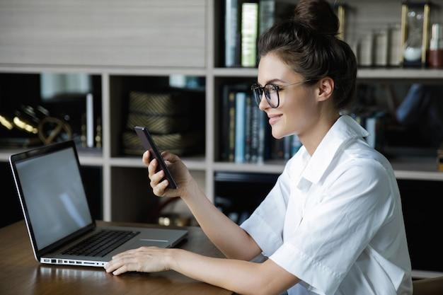 Jonge zakenvrouw praat door smartphone Premium Foto