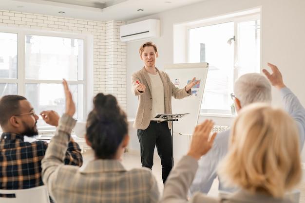 Jonge zelfverzekerde coach vraagt een van zijn studenten met opgeheven handen na het uitleggen van gegevens op het whiteboard Premium Foto