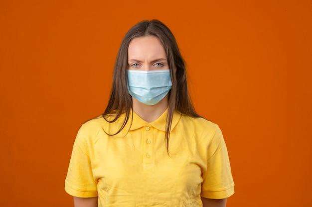 Jonge zieke vrouw die in geel poloshirt en medisch beschermend masker camera op oranje achtergrond bekijken Gratis Foto