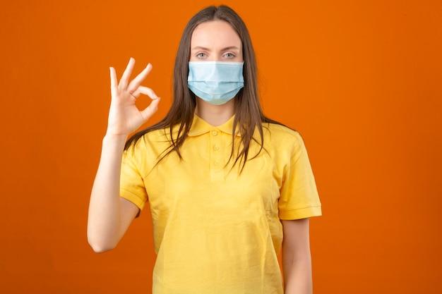 Jonge zieke vrouw in geel poloshirt en medisch beschermend masker die ok teken tonen die zich op oranje achtergrond bevinden Gratis Foto