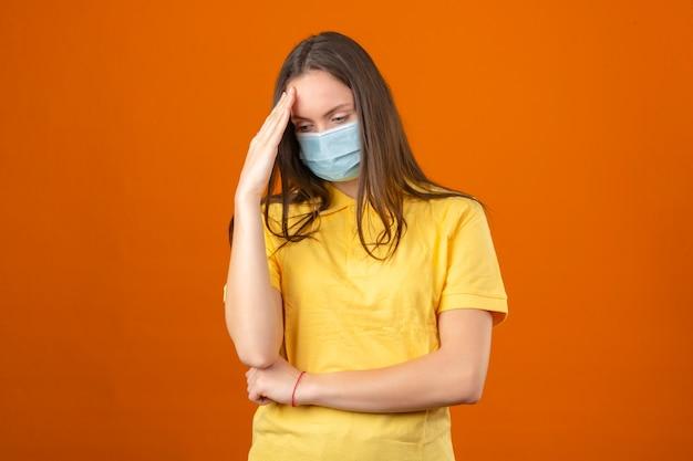 Jonge zieke vrouw in geel poloshirt en medisch beschermend masker wat betreft hoofd en het denken op geïsoleerde oranje achtergrond Gratis Foto
