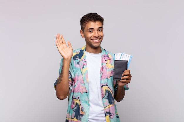 Jonge zuid-amerikaanse man lacht vrolijk en opgewekt, zwaait met de hand, verwelkomt en begroet je, of neemt afscheid Premium Foto