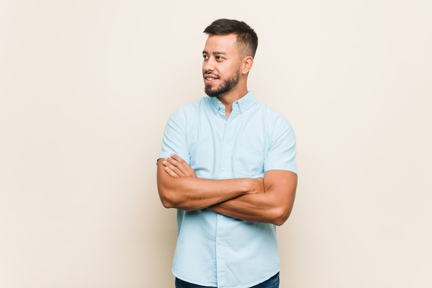 Jonge zuid-aziatische man die lacht vertrouwen met gekruiste armen. Premium Foto