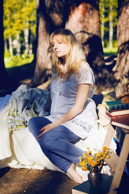 Jonge zwangere blonde vrouw slaapt in een bed in de natuur. het concept van een goede nachtrust Premium Foto
