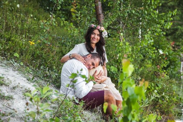 Jonge zwangere vrouw met haar echtgenoot die van de aard genieten die casual en stijljeans en wit t-shirt dragen. Premium Foto