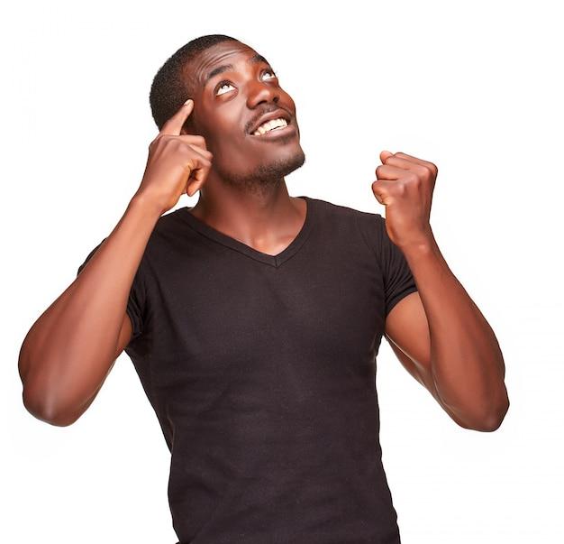 Jonge zwarte afrikaanse mens die en over iets denkt ophaalt Gratis Foto