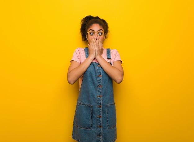 Jonge zwarte afro-amerikaanse meid met blauwe ogen erg bang en bang verborgen Premium Foto