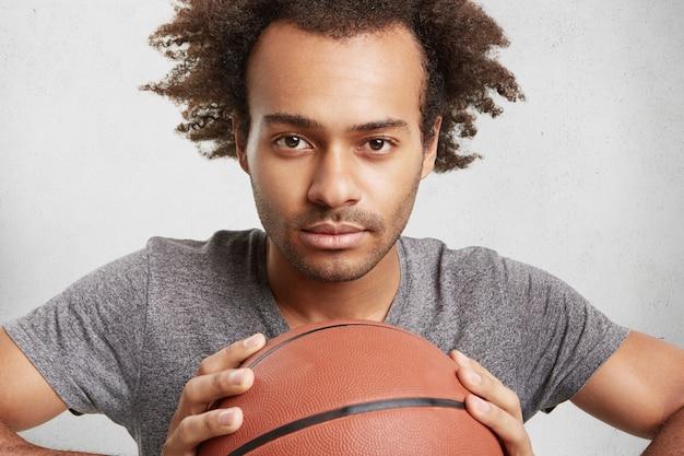 Jonge zwarte basketbalspeler houdt bal vast, kijkt zelfverzekerd Gratis Foto