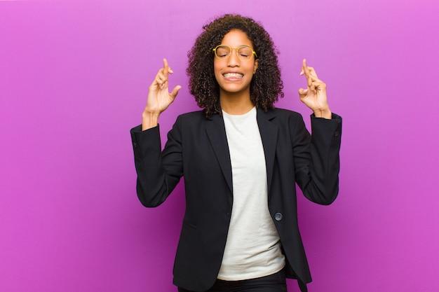 Jonge zwarte bedrijfsvrouw die en angstig beide vingers glimlacht kruist Premium Foto