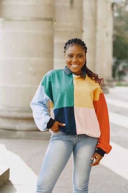 Jonge zwarte die met afrokapsel in stedelijke stad glimlacht. gemengd meisje in een kleurrijke trui. Gratis Foto