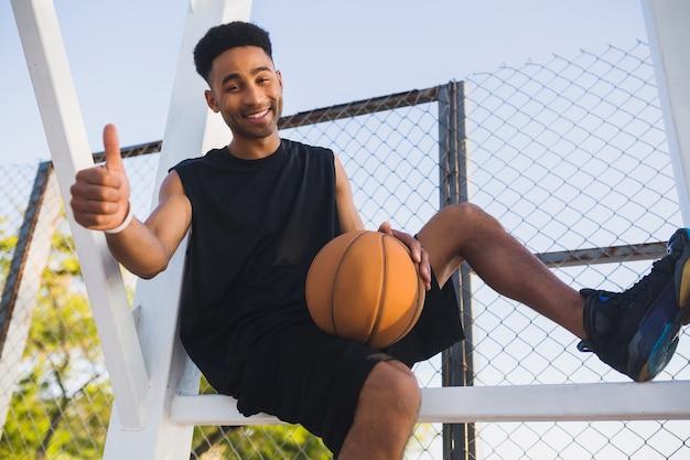 Jonge zwarte man aan het sporten, basketballen, actieve levensstijl, zomerochtend, glimlachend gelukkig met plezier Gratis Foto