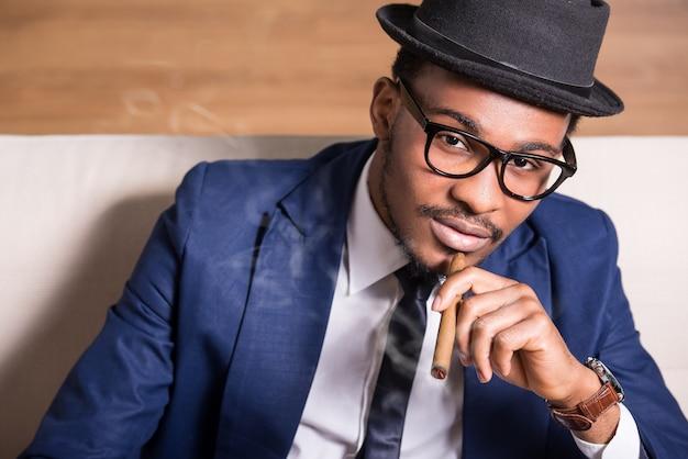 Jonge zwarte man draagt pak en hoed, het roken van een sigaar. Premium Foto