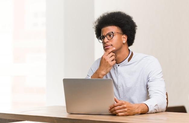 Jonge zwarte man met behulp van zijn laptop twijfelen en verward Premium Foto
