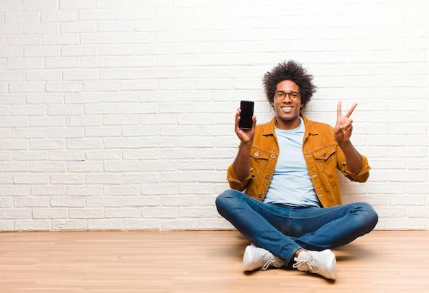 Jonge zwarte man met een slimme telefoon zittend op de vloer Premium Foto