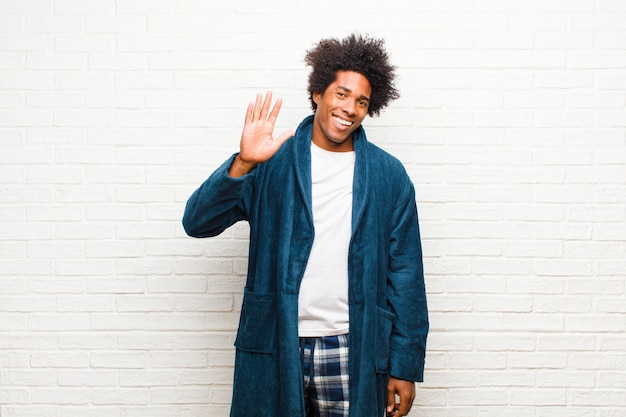 Jonge zwarte man met pyjama met jurk glimlachend gelukkig en vrolijk, zwaaiende hand, verwelkomen en begroeten, of afscheid nemen Premium Foto