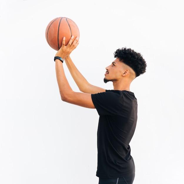 Jonge zwarte mens die basketbal voorbereidingen treft te werpen Gratis Foto