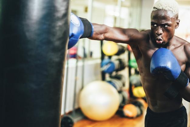 Jonge zwarte mens die binnen de gymnastiekclub van de opleidingsgeschiktheid in dozen doen Premium Foto