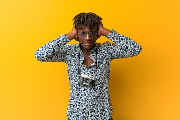 Jonge zwarte rastamens die een vakantie draagt kijkt die oren behandelen met handen die niet te hard geluid proberen te horen. Premium Foto