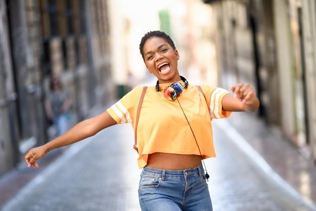 Jonge zwarte vrouw danst op straat in de zomer. Premium Foto