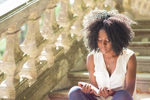 Jonge zwarte vrouw lezen boek op de trappen in park Gratis Foto