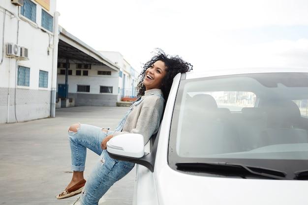Jonge zwarte vrouw met afro haar lachen en genieten van leunend op haar auto Gratis Foto