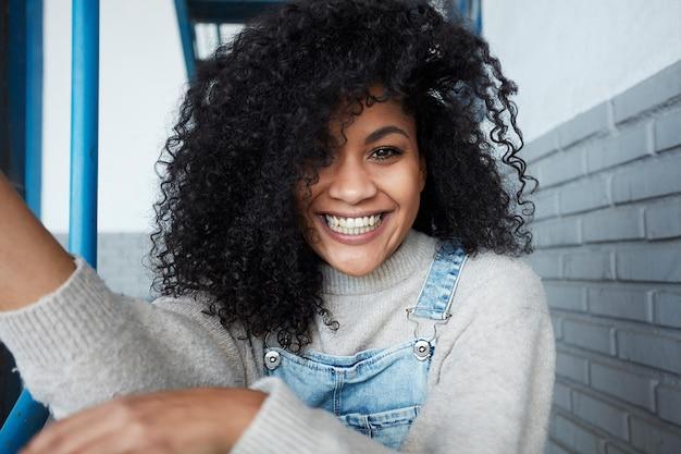 Jonge zwarte vrouw met afro haar lachen en genieten Gratis Foto