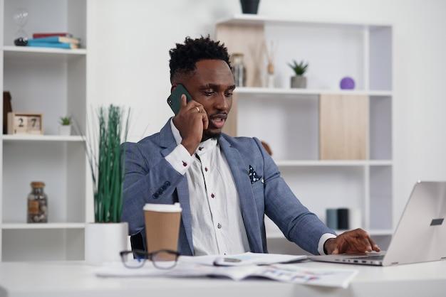 Jonge zwarte zakenman die op mobiele telefoon spreekt en aan laptop in modern wit bureau werkt, exemplaarruimte Premium Foto