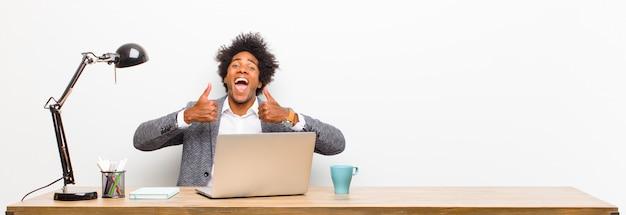Jonge zwarte zakenman glimlachend breed op zoek gelukkig, positief, zelfverzekerd en succesvol, met beide duimen omhoog op een bureau Premium Foto