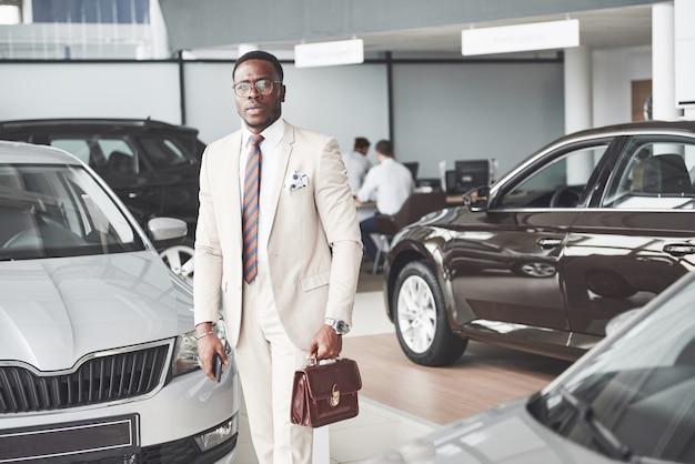 Jonge zwarte zakenman op autosalon. auto verkoop en huur concept. Gratis Foto