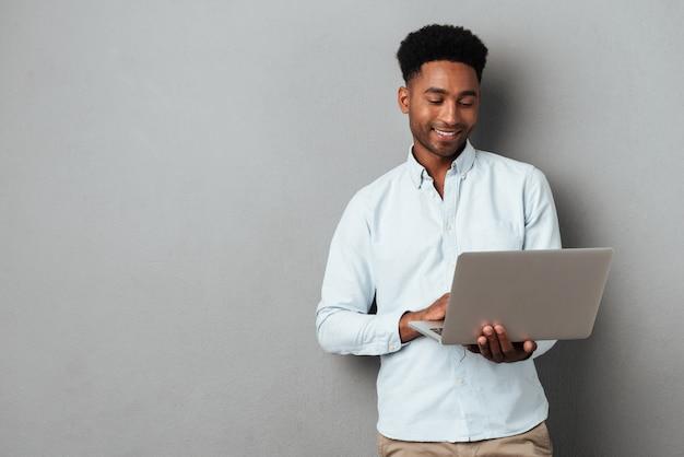 Jongelui die afrikaanse mens glimlachen en laptop met behulp van Gratis Foto