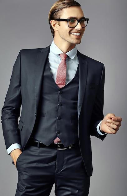 Jongelui die elegant knap zakenman mannelijk model in een kostuum en modieuze glazen glimlachen Gratis Foto