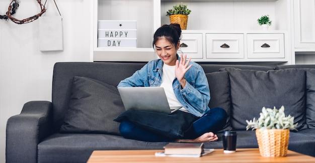 Jongelui die gelukkige mooie aziatische vrouw ontspannen thuis gebruikend laptop computer het werken en videoconferentievergadering. het jonge creatieve meisje zegt hallo en typend op toetsenbord. werk vanuit huis concept Premium Foto