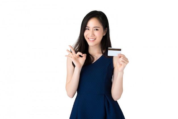Jongelui die mooie aziatische vrouw glimlachen die creditcard met okeygebaar tonen Premium Foto