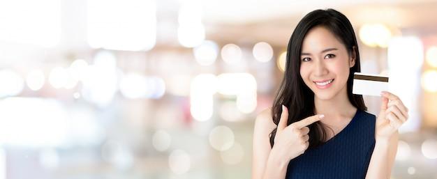 Jongelui die mooie aziatische vrouw glimlachen die creditcard ter beschikking aanbieden Premium Foto