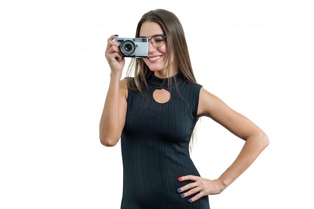 Jongelui die mooie vrouw die in zwarte kledingsglazen glimlachen fotocamera in haar handen houden, die foto nemen Premium Foto