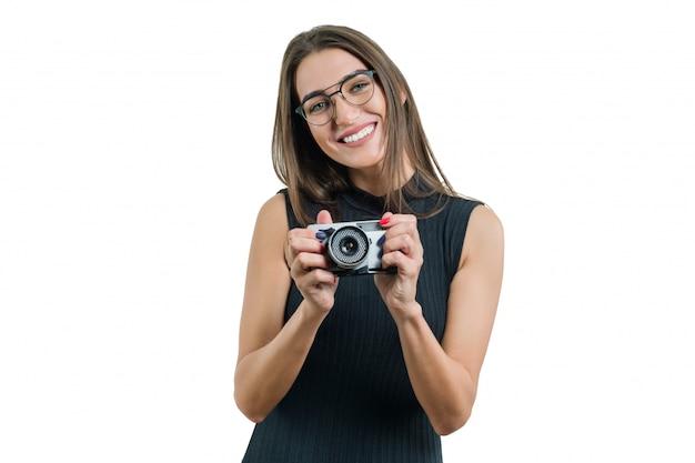 Jongelui die mooie vrouw die in zwarte kledingsglazen glimlachen fotocamera in haar handen houden Premium Foto