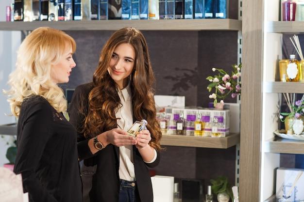 Jongelui die positieve verkoopster dienende klant in parfumwinkel glimlachen. Premium Foto