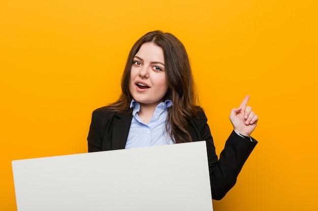 Jongelui plus grootte curvy vrouw die een aanplakbiljet houden glimlachend vrolijk wijzend met weg wijsvinger. Premium Foto