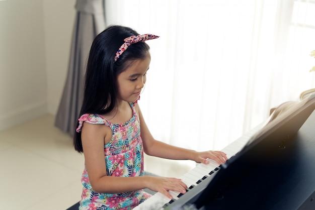 Jongelui weinig aziatisch leuk meisje die elektronische piano thuis spelen. Premium Foto