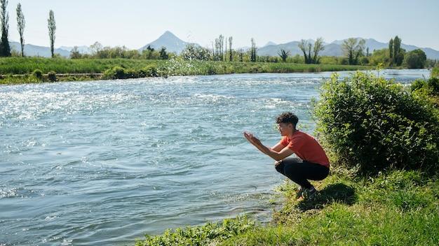 Jongeman spatten water uit de rivier Gratis Foto