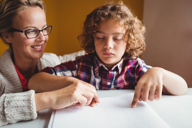 Jongen die braille gebruikt om te lezen Premium Foto