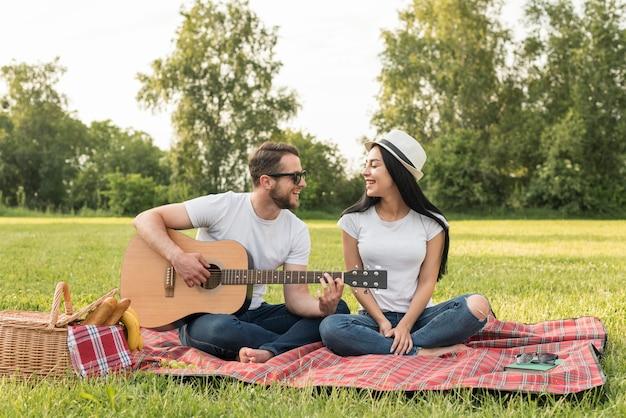 Jongen die de gitaar voor zijn meisje op een picknickdeken speelt Gratis Foto