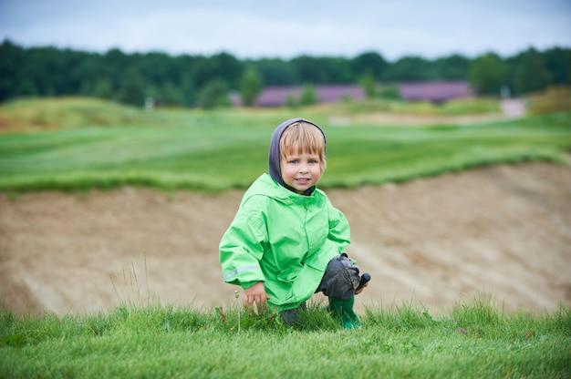 Jongen die de golfbaan loopt Premium Foto