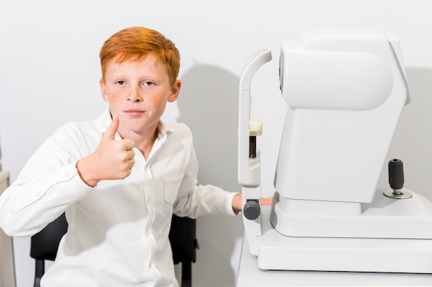 Jongen die duim op gebaarzitting tonen dichtbij refractometermachine bij optiekkliniek Gratis Foto