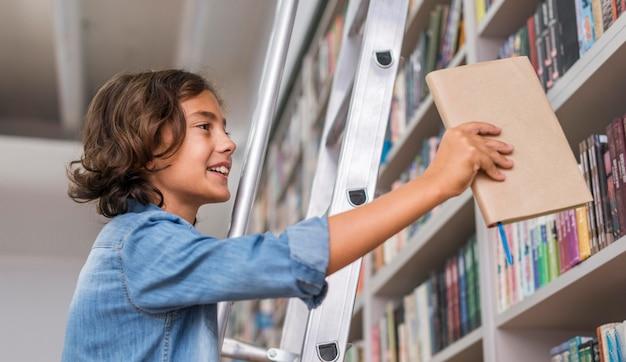 Jongen die een boek terug op de plank legt Gratis Foto