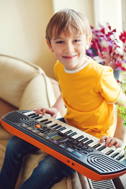 Jongen die een muziekinstrument leert te spelen Premium Foto